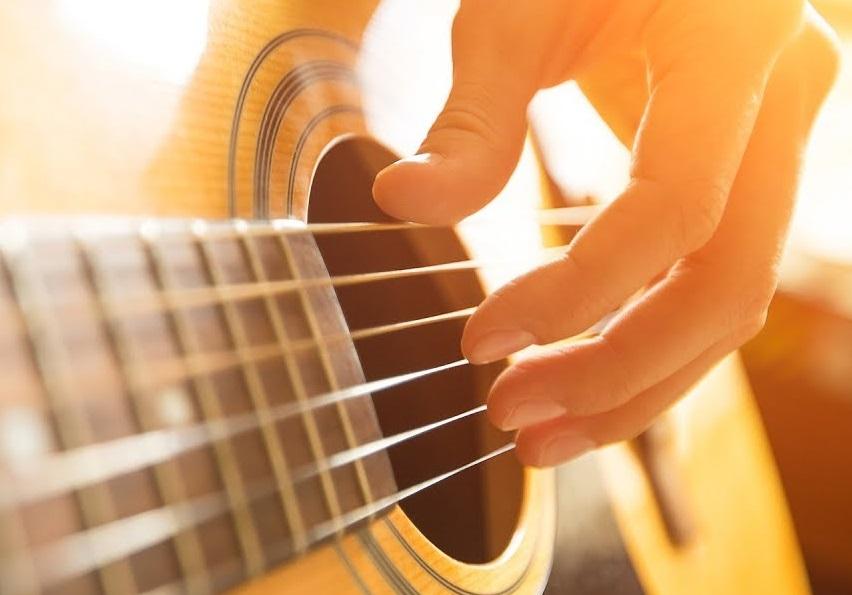Main jouant de la guitare acoustique