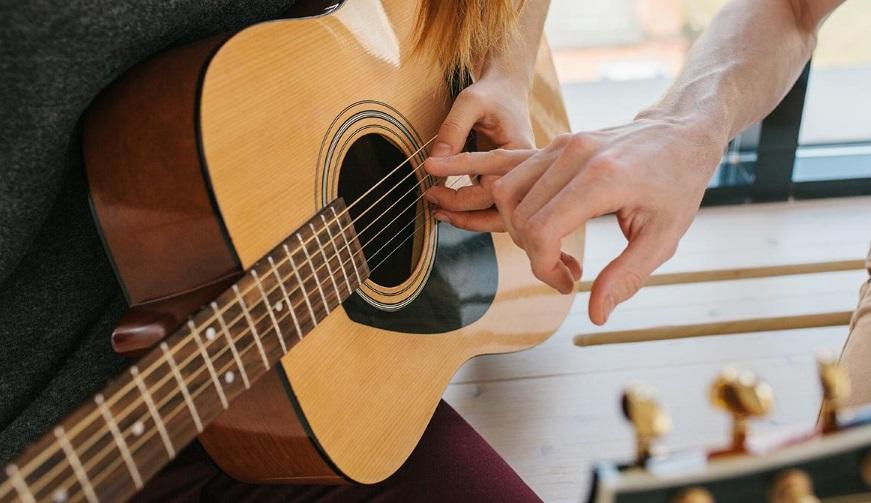 Personne apprenant à jouer de la guitare