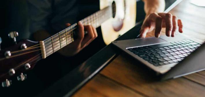 musicien utilise guitare et ordinateur